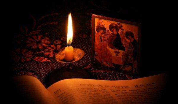 Горящая свеча перед иконой «Три ангела»